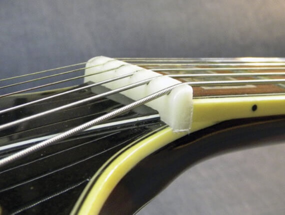 Выпуклость на верхнем порожке гитары